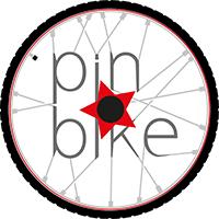 """Una ruota di bicicletta con la scritta """"pin * bike"""" incastrata fra i raggi"""